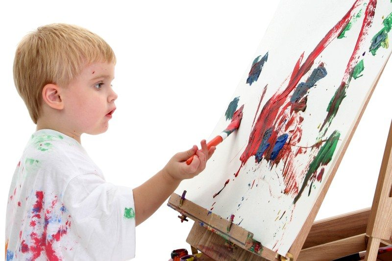caucasian toddler boy painting at easel